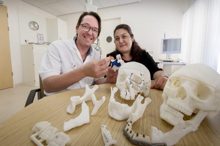 Kaakchirurg Barry Kolenaar en patiënte bekijken geprinte mallen en implantaten