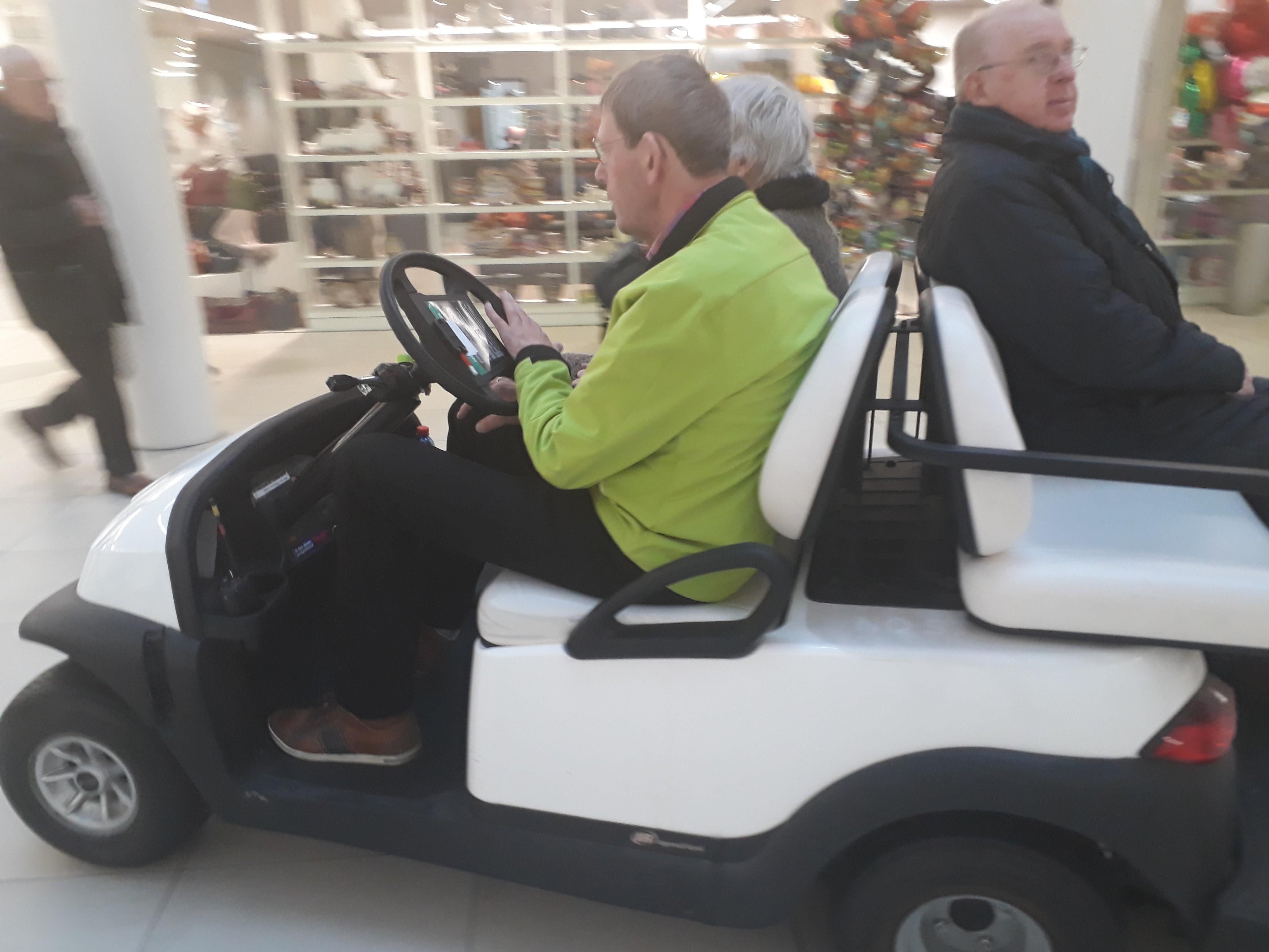 Vrijwilliger op golfkar met patiënten